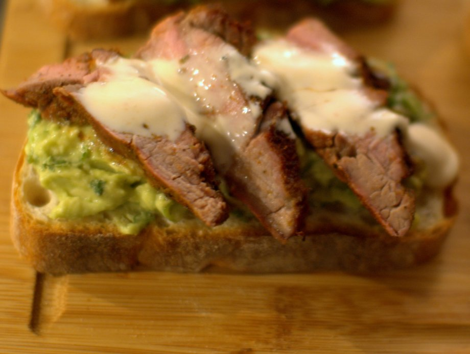 grilled flank steak sandwich with avocado and spice crema
